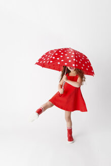 Girl in a red dress and red rain boots holding red umbrella in front of white background - LITF00510