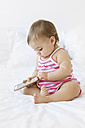 Baby girl sitting on white bed playing with smartphone - LITF00516