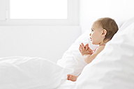 Baby girl sitting between pillows on a white bed - LITF00522