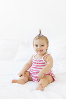 Portrait of smiling baby girl sitting on a white bed sticking out tongue - LITF00528