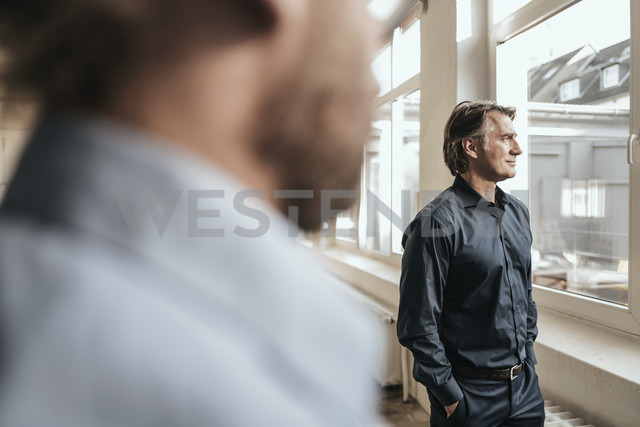 Mature businessman looking out of window - JOSF00669