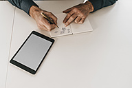 Man drawing geometric shapes into notebook next to tablet - JOSF00675