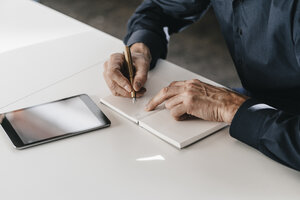 Businessman writing in notebook next to tablet - JOSF00696