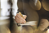 Hand of businessman writing with golden fountain pen on notepad - KNSF01134