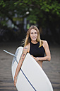 Portrait of smiling woman carrying surfboard on the beach - KNTF00674
