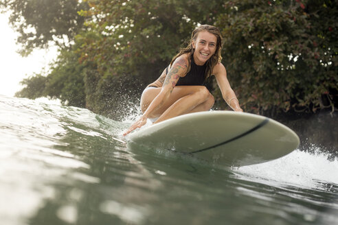 Indonesia, Java, happy woman surfing - KNTF00686