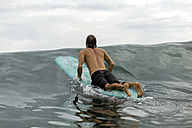 Indonesia, Java, man lying on surfboard on the sea - KNTF00701