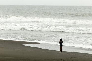 Indonesia, Java, woman at ocean coastline - KNTF00728