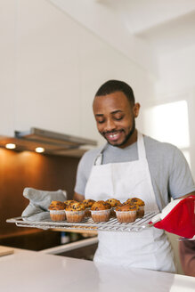 Young man baking cup cakes at home - VABF01234