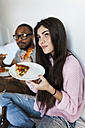 Young couple sitting at home eating pizza - VABF01249