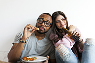 Young couple at home eating pizza and drinking beer - VABF01252