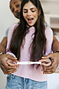 Young couple holding positive pregnancy test - VABF01255