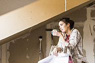 Young woman renovating her new home, holding construction plan - UUF10075