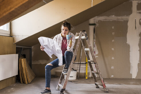 Young woman renovating her new home, holding construction plan - UUF10078