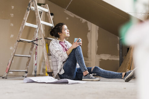 Young woman renovating her new home, holding construction plan - UUF10081