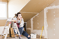Young woman contemplating the renovation of her new home - UUF10084