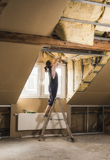 Young woman mounting insulation in her new home - UUF10090