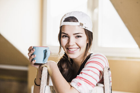 Young woman on construction site holding cup of coffee - UUF10096
