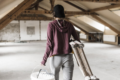 Young woman on construction site carrying ladder and paint bucket - UUF10123