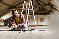Independent young woman renovating her new home, sittiing on floor with cup of coffee - UUF10138