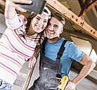 Young couple renovating their new home, taking smart phone selfies - UUF10144