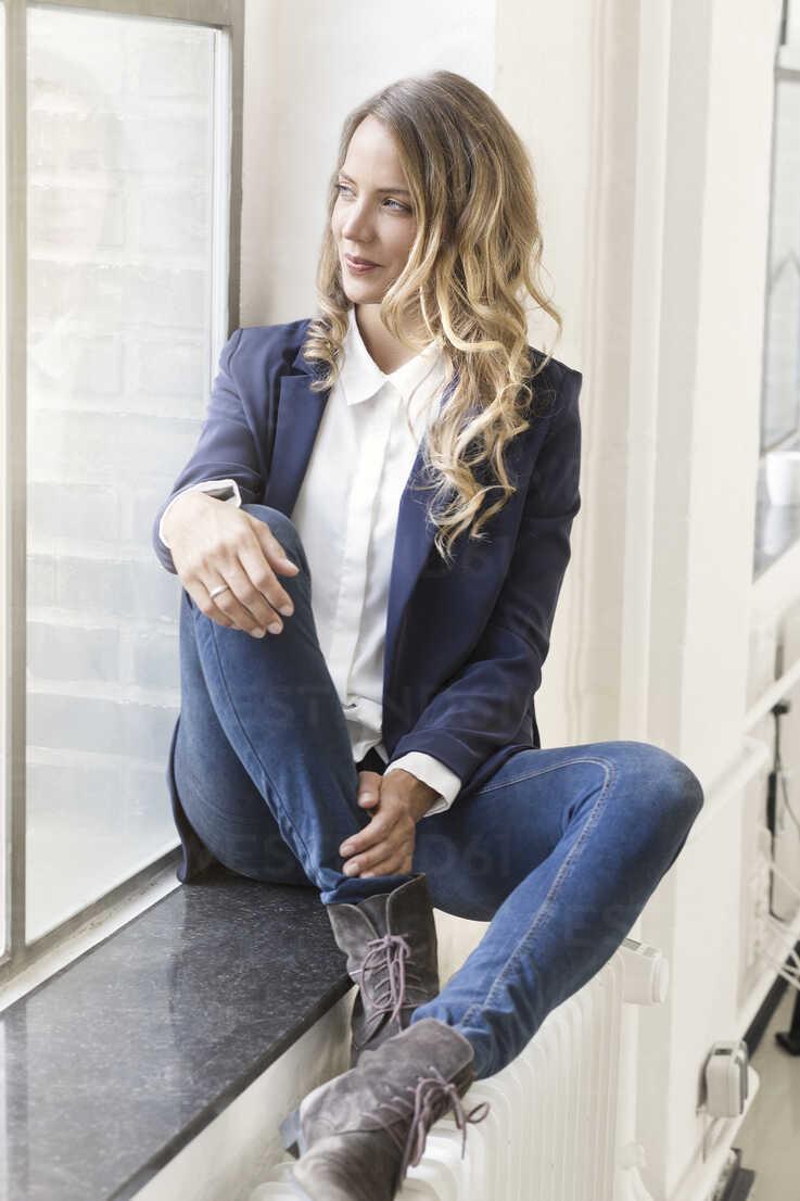 Businesswoman sitting on window sill of her office - SBOF00297 - Steve Brookland/Westend61