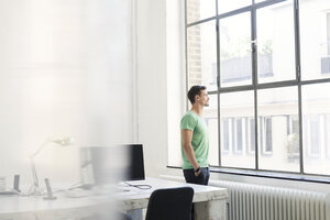 Young businessman looking out of office window, looking pensive - SBOF00306