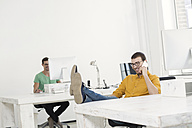 Two businessmen working together in office - SBOF00309