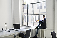 Young businessman looking out of office window - SBOF00327