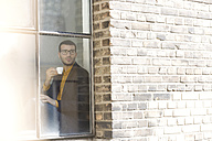 Businessman sitting on window sill, drinking coffee - SBOF00330