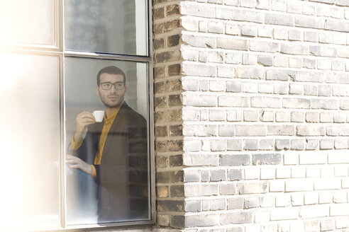 Businessman sitting on window sill, drinking coffee - SBOF00330
