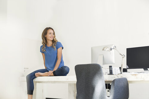Casual businesswoman in office, sitting on desk, looking confident - SBOF00333