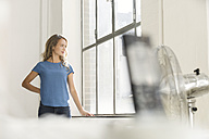 Casual businesswoman in office looking out of window - SBOF00336