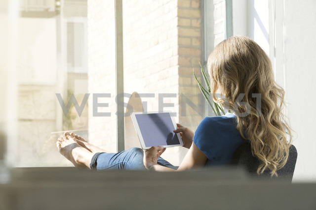 Casual businesswoman in office using digtal tabet with feet on window sill - SBOF00339 - Steve Brookland/Westend61