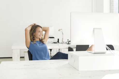 Casual businesswoman sitting in office - SBOF00342