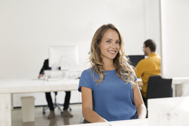 Casual businesswoman sitting in office, colleagues working in background - SBOF00354