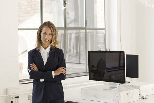 Businesswoman standing in her office with arms crossed - SBOF00357