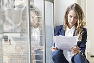 Businesswoman sitting in her office, reading papers - SBOF00360