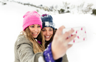 Two friends taking smart phone selfies in the snow - MGOF03056