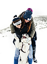 Young couple playing with their dog in the snow - MGOF03074