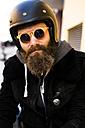 Portrait of bearded biker wearing helmet and sunglasses - KKAF00493