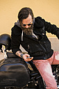 Bearded biker on his motorcycle looking at cell phone - KKAF00499