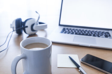 Cup of coffee, headset, smartphone, ballpen, adhesive note and laptop on desk - TCF05312