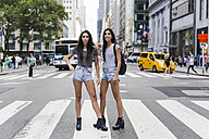 USA, New York City, two twin sisters standing on zebra crossing in Manhattan - GIOF02172