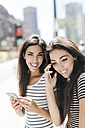 USA, New York City, two happy twin sisters with cell phones in Manhattan - GIOF02181