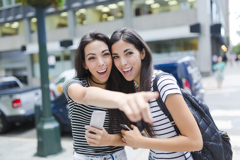 USA, New York City, two happy twin sisters with cell phones in Manhattan - GIOF02187