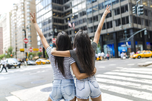 USA, New York City, back view of two young women in Manhattan having fun - GIOF02193