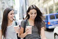 USA, New York City, two happy twin sisters on the go in Manhattan with takeaway drink - GIOF02196