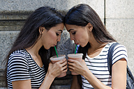 Two twin sisters having a takeaway drink - GIOF02199