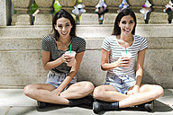Two happy twin sisters sitting outdoors having a takeaway drink - GIOF02202